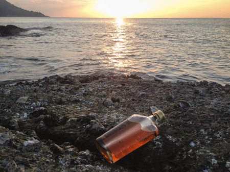 whisky in flat Bottles on rock beach with sunset