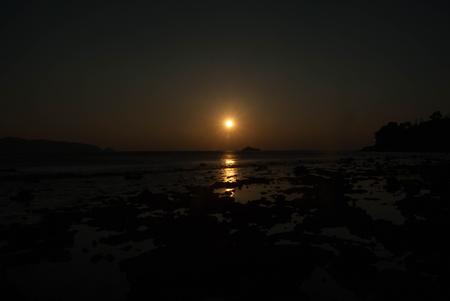 sunset on the rock beach Stock Photo