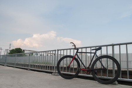 Black and red sport professional high speed fixed gear track bicycle standing near a fence and blue sky background
