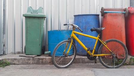 old yellow bike near dustbin