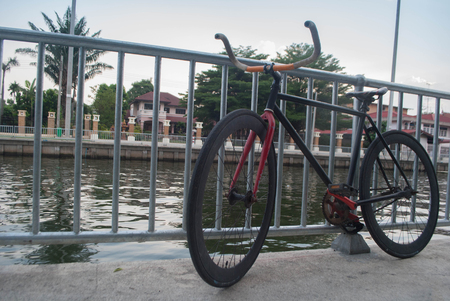 Black and red sport professional high speed fixed gear track bicycle standing near a fence and river background Stock Photo