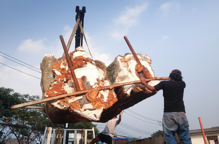 Human loading cut tree trunks imitation on Great white auto truck crane Stock Photo
