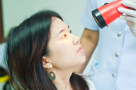 dilate: doctor shines a light into eye to check vision ocular health