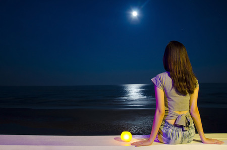 moon chair: girl siting on the beach at night