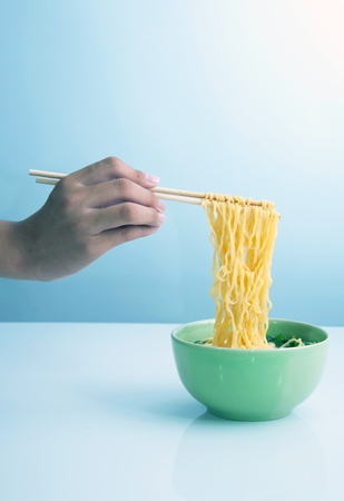 instant noodles: yellow noodle soup in bowl and hand holding chopstick