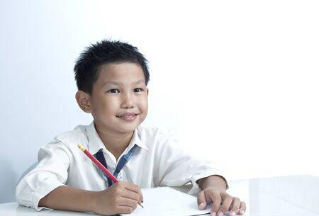niños platicando: Un niño feliz asiática sosteniendo un lápiz sobre fondo blanco
