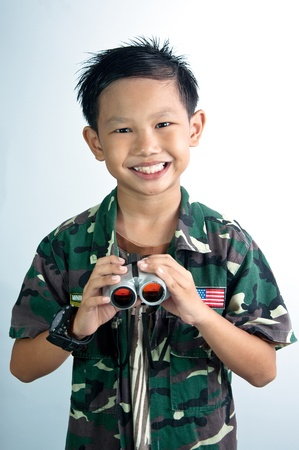A Asian boy in Soldier suite holding binocular photo