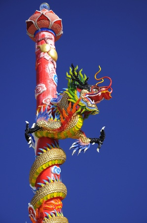 Chinese dragon on the pole blue sky background photo