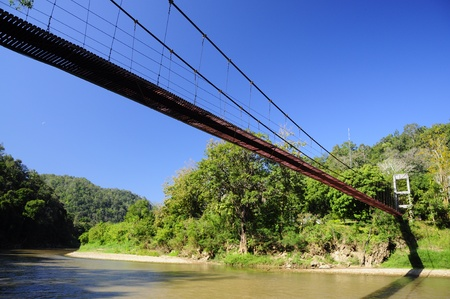 The Rope bridge across the river to the jungle, North Thailand photo