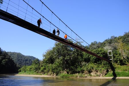People walk across the rope bridge, north Thailand shot1 photo