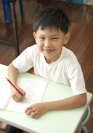 The Asian boy writeing in classroom photo
