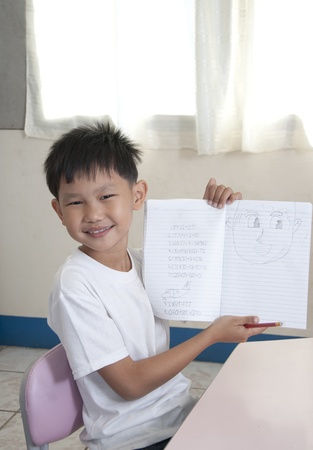 Asian kid holds home work in classroom photo