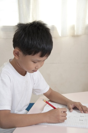Asian kid do home work in classroom photo