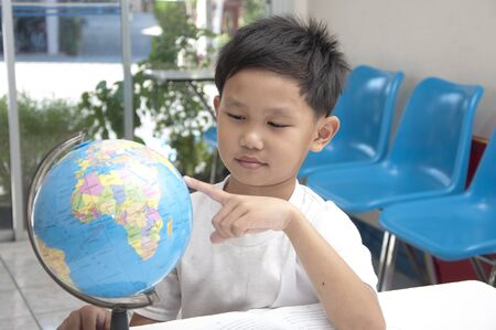 The Asian boy pointing at globe model. photo