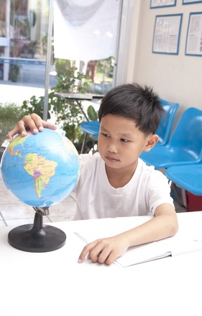 The Asian kid in library with globe model. Stock Photo - 12306428