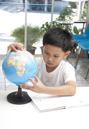 child studying: The Asian kid in library with globe model. Stock Photo