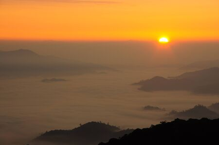 Beautiful sky with sunrise over the mist mountain at national park, Thailand  photo