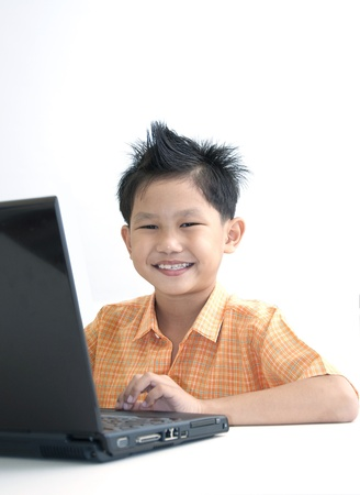 Smailing boy uses computer laptop  photo