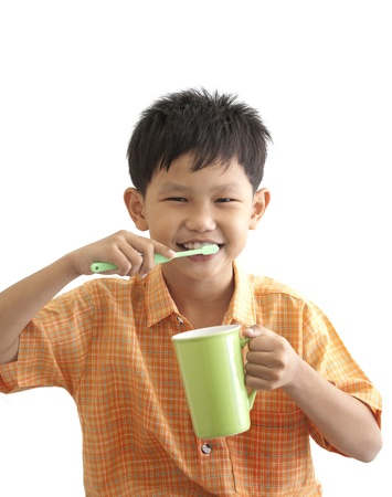 Asian boy brushing teeth on white background photo