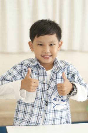 thumps up: Asian boy thumps up in classroom Stock Photo
