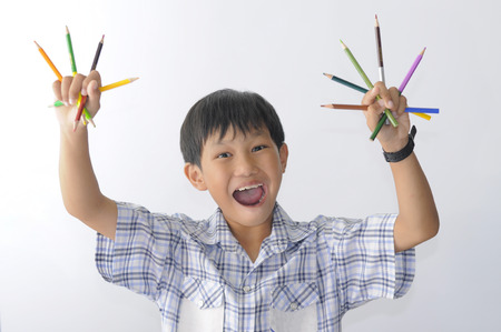 drawing table: Asian boy is showing his color pencils