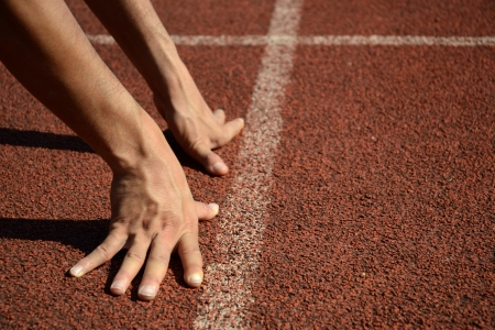 pista de atletismo: Ejecute Mans mano en posición de Running Start en Pista de atletismo. Mano Pista de atletismo White Lines.