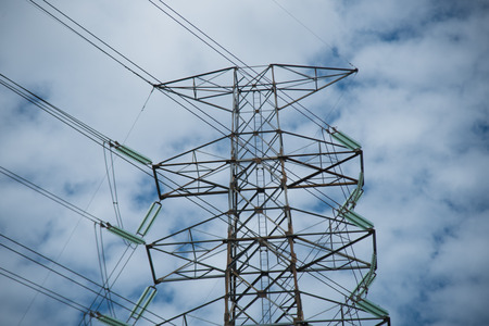 Hi-voltage electrical pylons and Hi-Power Transmission electric Line on blue sky background,Selective focus,Too soft blur Stock Photo