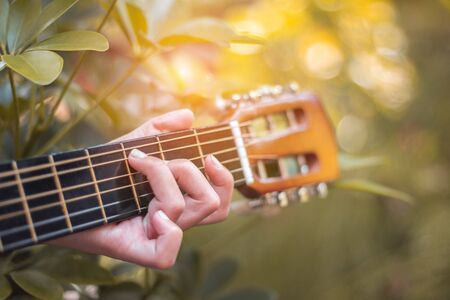 Close up hand of woman playing acoustic guitar.