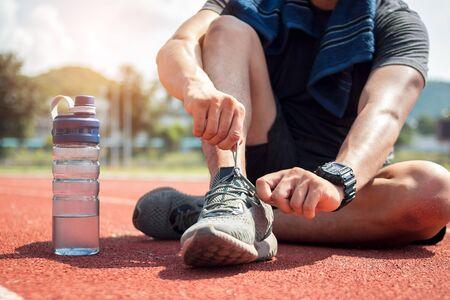 Man runner tying shoelaces on track stadium.