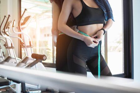 Slim body woman measuring her waist at gym.