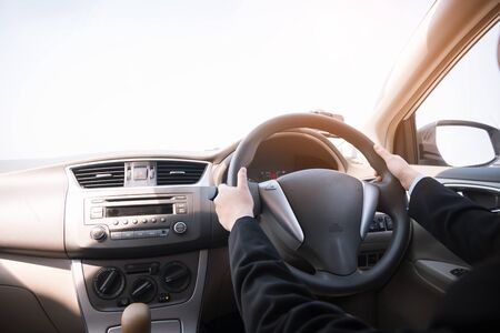 Woman driving her car, hands holding steering wheel. Archivio Fotografico