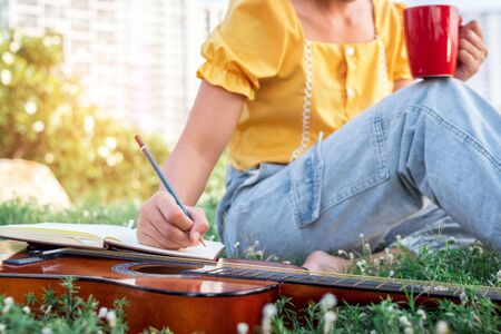 Songwriter writing on notebook with acoustic guitar, holding coffee cup.