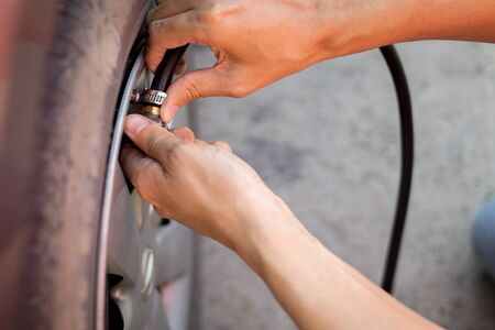 Close up hand of man inflating tire. Stock Photo