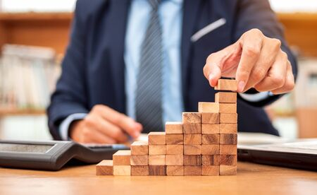 Concept of Business growth, Businessman success for career, Close up hand of man has piling up and stacking a wooden block.