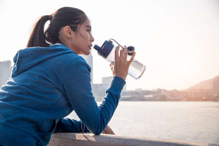 Tired Young woman is drinking water after run in the morning. Standard-Bild
