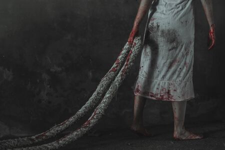 Murderer woman holding rope with blood after kill.