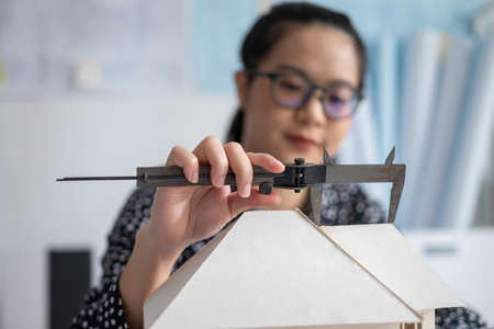 Engineer using Vernier caliper to measuring architectural model.