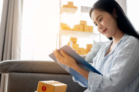 Small business owner woman is checking product with clipboard to send to customer for the online order