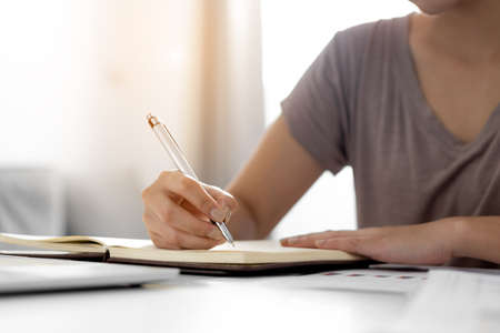 Close up business women hand is writing notebook with laptop at home