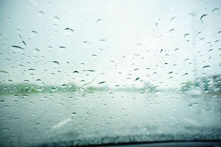 soft rain drops on vehicle's front glass in a day time on the highway