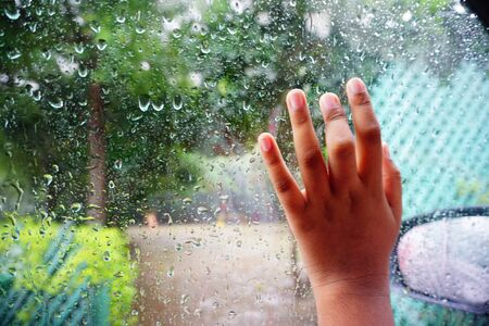 there is a hand on a glass with rain drops and a view of the park behind it. Stock fotó
