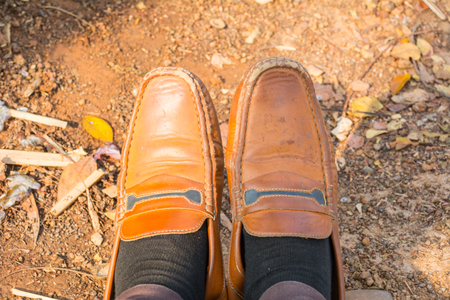 muddy clothes: still life with brown leather shoes old