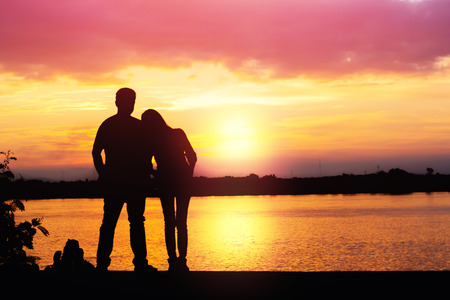 Silhouette of loving couple standing riverside and beautiful sunset background. Stock Photo