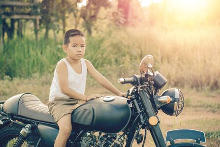 Little kid  on classic motocycle in park.