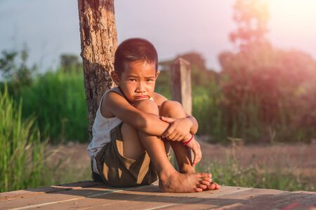 Little boy unhappy sitting alone on abandoned temporary housing. Stock Photo