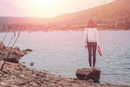 Young beautiful hipster woman. Standing alone on the river.