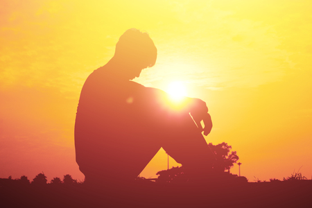 sadly: Silhouette of a young boy sitting sadly on sunset. Stock Photo