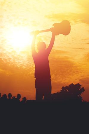 Silhouet van jonge muzikant met een gitaar op zonsondergang.