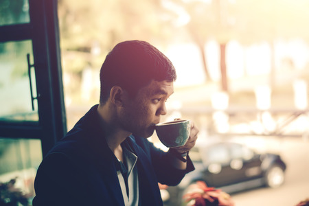 Young businessman looking to relax from work by sipping coffee.