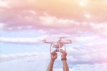 controlled: Man holding drone with hand outdoor and sunset sky background.